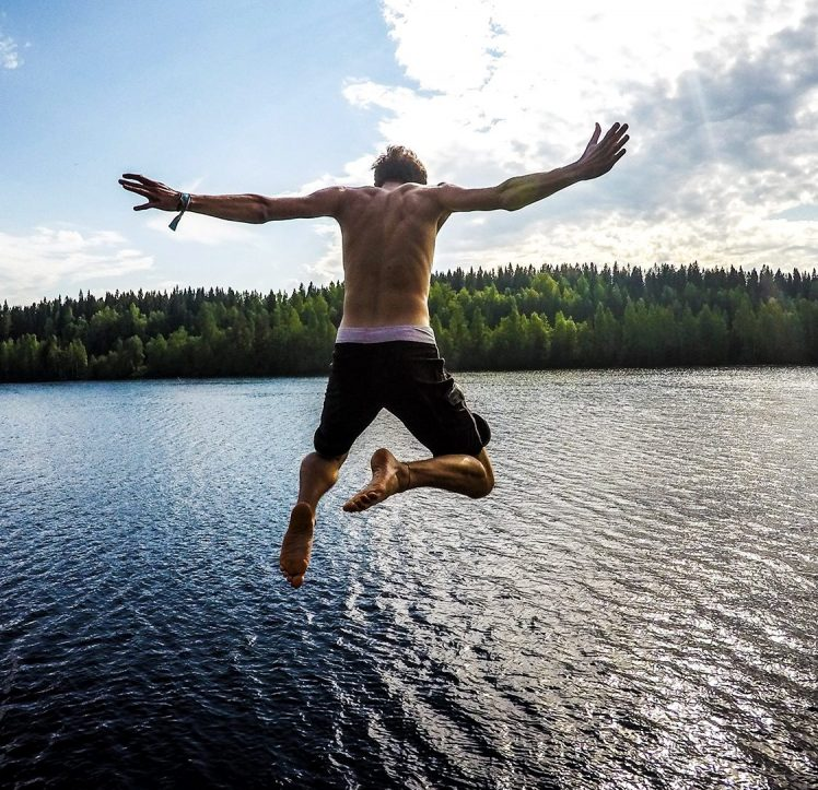 Muscular young man jumping into a lake